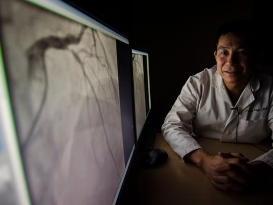 "Dr. Prospero Gogo looks at scans from Hugh Gibson's procedure at the University of Vermont Medial Center in Burlington. Two stents were inserted into Gibson's heart arteries to remove serious blockages, one in a major artery commonly known among medical professionals as the ""widow maker."""