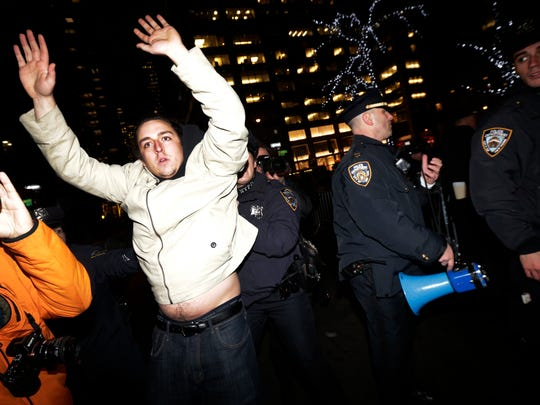A man, left, holds his hands up as New York City Police officers secure a street near Rockefeller Center during a protest after it was announced that the police officer involved in the death of Eric Garner is not being indicted, Wednesday, Dec. 3, 2014, in New York. A grand jury cleared the