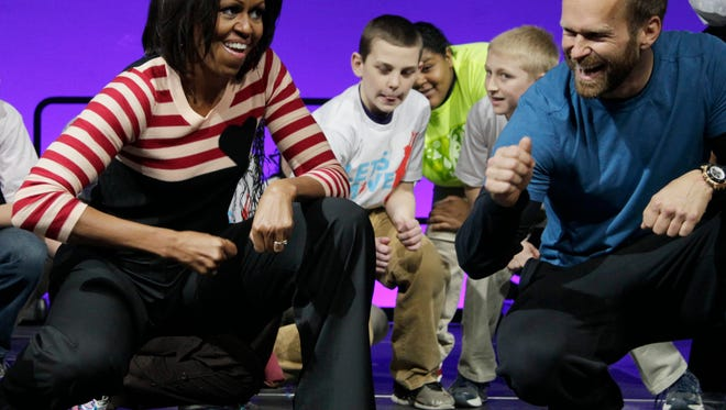 "FILE - In this Feb. 9, 2012, file photo, first lady Michelle Obama and Bob Harper of ""The Biggest Loser,"" right in blue shirt, do the Interlude dance during a Let's Move event with children from Iowa schools at the Wells Fargo Arena in Des Moines, Iowa. Harper tells TMZ he suffered a heart attack and was hospitalized for several days in February 2017. (AP Photo/Carolyn Kaster, File)"