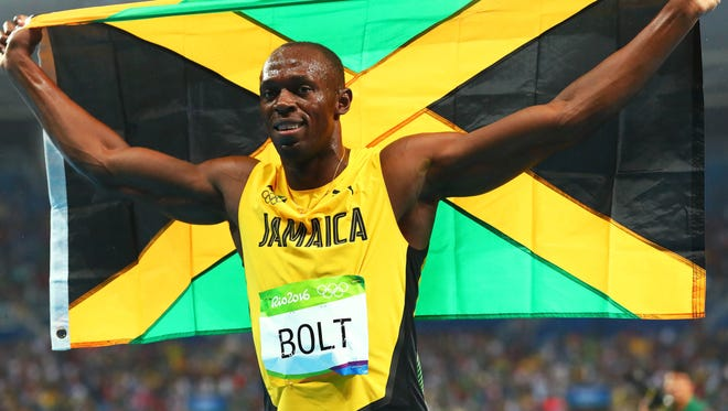 Usain Bolt celebrates winning the men's 200 meters for the third consecutive Games.