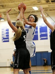 Launching a shot in her first varsity game is Salem freshman Mahrianna Petree (No. 21). Guarding her for Plymouth is Hannah Badger (No. 5).
