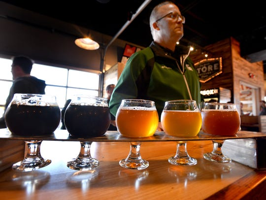 A beer sampler flight in the light at the grand opening