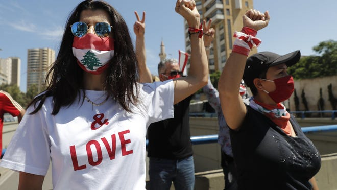 Anti-government protesters wearing masks to help curb the spread of the coronavirus shout slogans during a protest against a general amnesty law that is being proposed in parliament, in Beirut, Lebanon, Thursday, May 28, 2020.