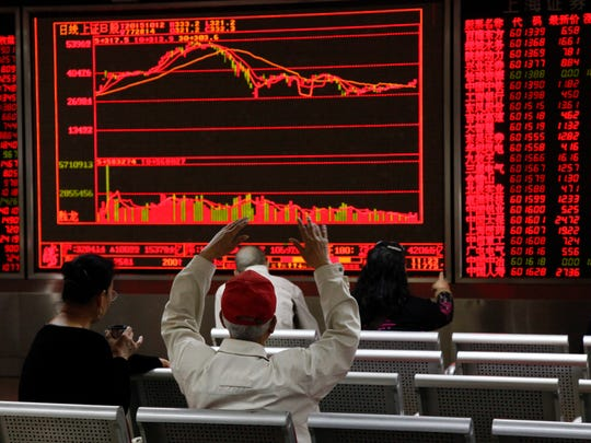 Investors monitor stock market data displayed on an
