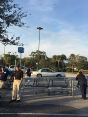 Employees from Walmart and Sam's Club on State Road 60 west of Vero Beach wait in the parking to be let back into the stores after they were evacuated Thursday, Jan. 19, 2017, following a bomb threat.