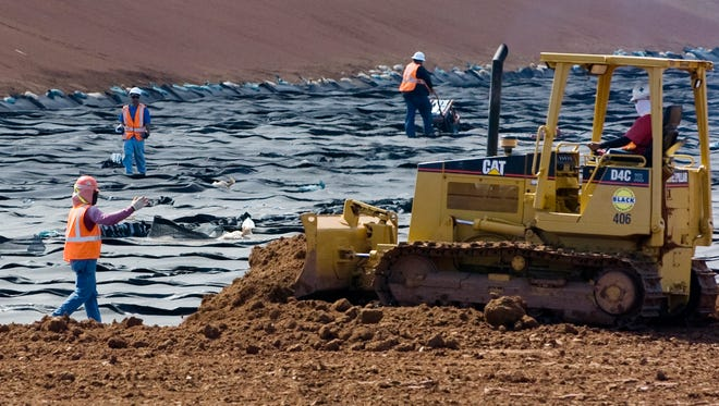 In this file photo, a construction crew works on the geo-composite layer on Cell 1 of the Layon Landfill.