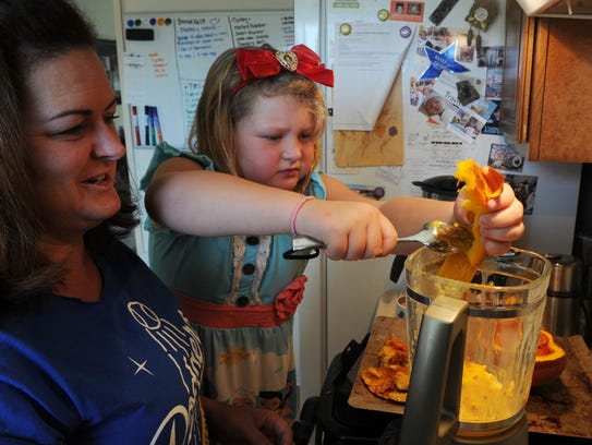 Jayme Hofteig and her daughter, Emma Hofteig, carry on a tradition as they make a pumpkin pie for Thanksgiving.