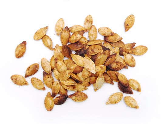 A pile of pumpkin seeds isolated on white