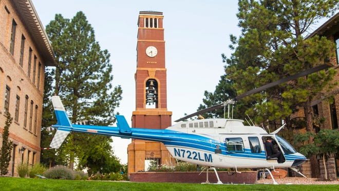 A helicopter sits in front of the bell tower on the campus of Southern Utah University, Wednesday, Aug. 24, 2016.