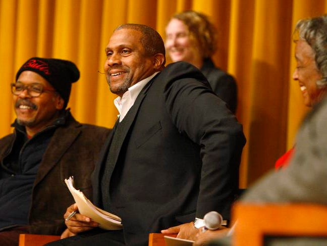 """Tavis Smiley, center, starts the night off with a few light moments as he sits with the """"Pioneers"""" panel during the State of Race in Rochester panel discussion held Thursday night at East High in Rochester. Seated with Smiley are Carvin Eison, left, Dr. Ruth Scott, second from right, and Julio Vazquez, right."""