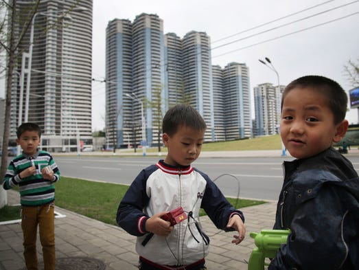 Boys play on the sidewalk along Changjon Street lined