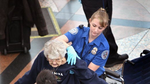A Transportation Security Administration agent performs an enhanced pat down on an elderly traveler at the Denver International Airport