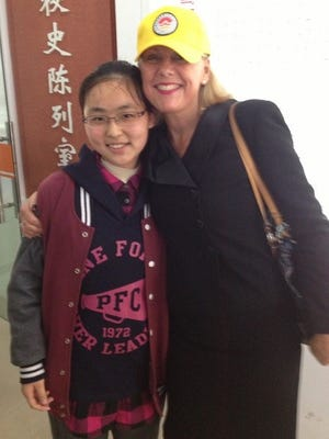 Wausau School District superintendent Kathleen Williams with a student at sister school Jiyang High School during an April 2015 trip to China.