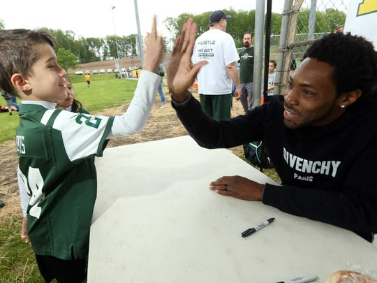 Robert Studier, 7, gets a high-five from former New York Jets cornerback Antonio Cromartie as sister Gabriella looks on. Cromartie greeted participants and signed autographs at Rockaway Twp Rockets Punt, Pass, and Kick contest at Peterson Field on May 20, 2017.