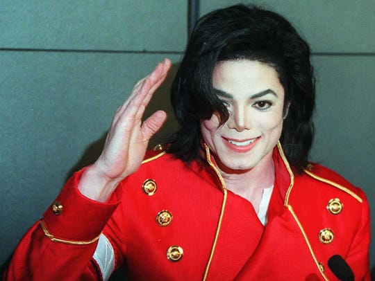 Michael Jackson waves to photographers during a press conference in Paris on March 19, 1996.