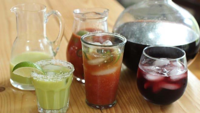 Pitcher cocktails: from left, cilantro corn margaritas, micheladas and hibiscus coolers.