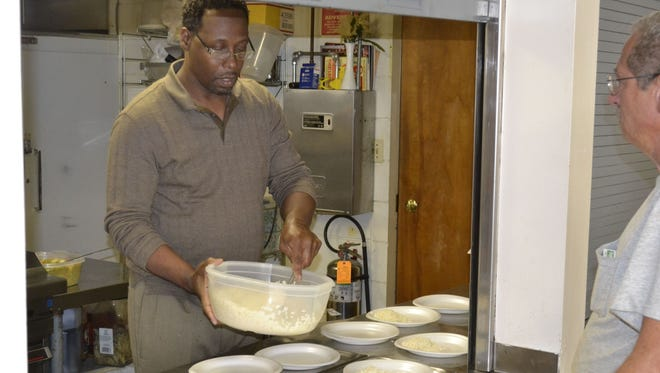 Pastor Manuelus Reacco served food to guests at Transformation House in 2014, when it was located at 436 S. Jefferson St.