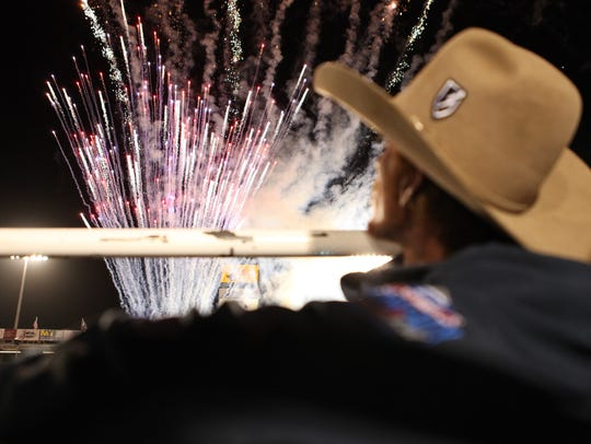 A cowboy watches the fireworks on Friday night at the
