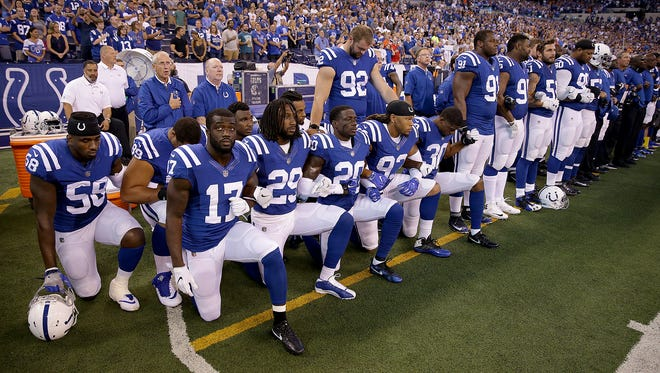 Several Indianapolis Colts players kneel during the national anthem before the start of their game against the Cleveland Browns at Lucas Oil Stadium Sunday, Sept. 24 2017.