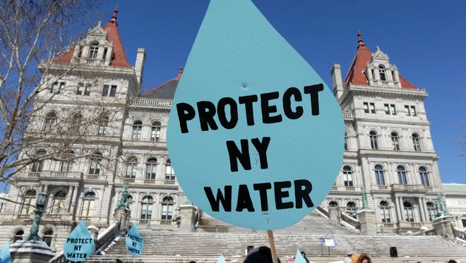 A man carries a sign before a rally opposing the Constitution Pipeline outside the state Capitol on Tuesday, April 5, 2016, in Albany, N.Y. (AP Photo/Mike Groll)