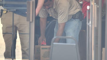 Federal agents investigate Sunbelt Tax Service on McDowell Road in Jackson on Wednesday.