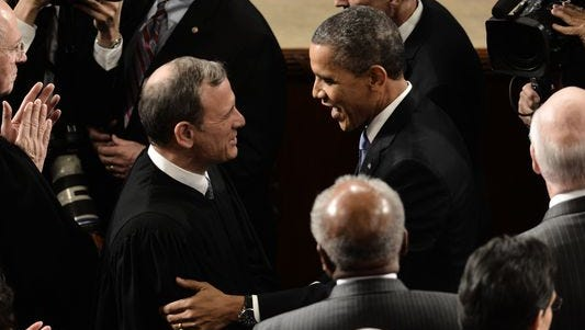 Chief Justice John Roberts and President Obama share an embrace at the State of the Union address in 2013.