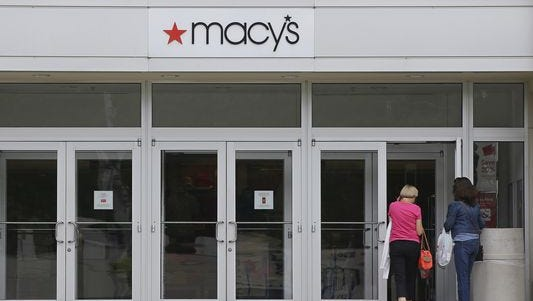 Shoppers walk into a Macy's department store.