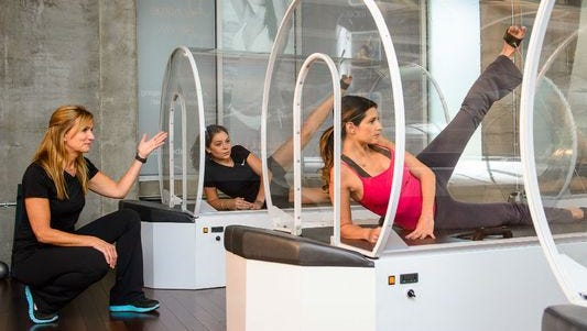 During the heated pod machine workout, you lie inside what looks like a glass capsule from a futuristic gym, and you exercise for 30 minutes using weight pulleys and resistance bands.