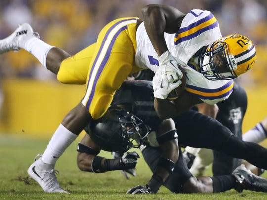 LSU running back Leonard Fournette (7) is tackled by Texas A&M defensive back Armani Watts during the first half an NCAA college football game in Baton Rouge, La., Saturday, Nov. 28, 2015. (AP Photo/Jonathan Bachman)