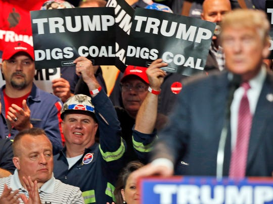 Coal miners wave signs as then-Republican presidential candidate Donald Trump speaks during a rally in Charleston, West Virginia on May 5, 2016.
