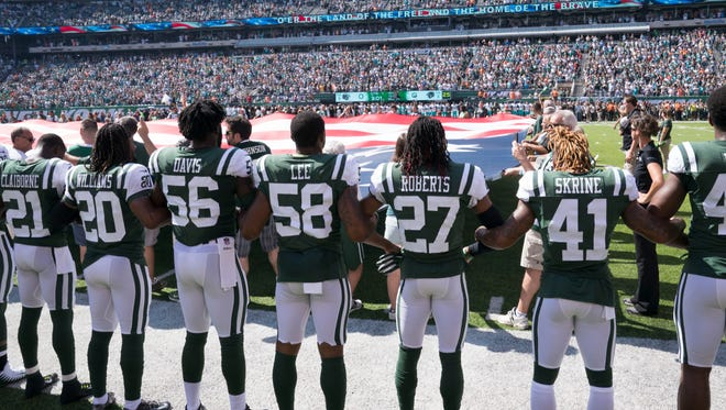 September 24, 2017; East Rutherford, NJ, USA; New York Jets players lock arms during the national anthem before the game against the Miami Dolphins at MetLife Stadium. Mandatory Credit: Kyle Terada-USA TODAY Sports