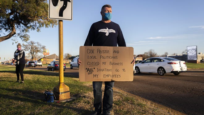 """""""I'm out here to support my employees,"""" said Scott Weitekamp, the owner of Crows Mill Pub, as he holds a sign at the corner of South Sixth Street and Stevenson Drive with a sign asking for donations to help support his employees after shutting down his bar as mitigations were put in place by Gov. JB Pritzker in the battle against the COVID-19 pandemic, Friday, Nov. 13, 2020, in Springfield, Ill. """"If I sit out here for four hours for my employees, it's something that might pay their groceries or might pay a bill and the support is unbelievable. I'm retired and I'm out here for them."""""""