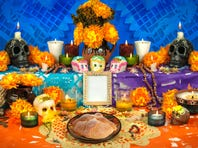 Traditional Mexican Day of the Dead altar with sugar skulls and candles.