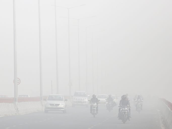 Motorists drive surrounded by smog in New Delhi, India,