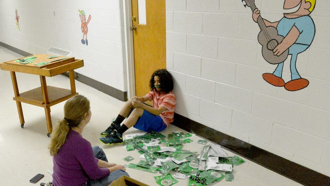 Rakim Al-hajj, 11, of Waynesboro sits with back to the wall helping Susan Roberts of Waynesboro Parks and Recreation to sort Saint Patrick's Day decorations found in a box at the Rosenwald Community Center on Saturday, March 1, 2014.