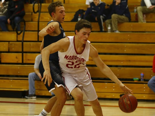Marathon's Nathan Stoffel(22), right, dribbles through Columbus Catholic's Tyler Fuerlinger(35) during Tuesday night nonconference boys basketball game match at Marathon High School.