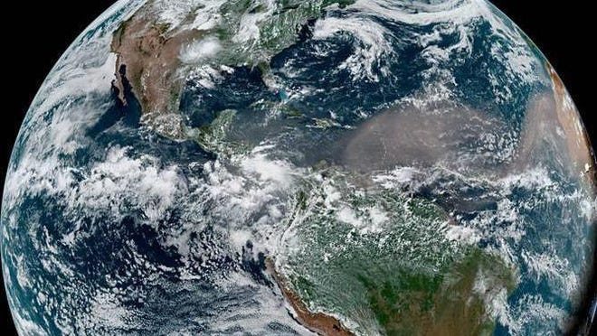 An image from June 21 shows the cloud of dust associated with the Saharan Air Layer traveling into the Caribbean Sea toward the Gulf of Mexico.