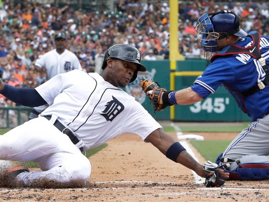 Detroit Tigers' Justin Upton beats the tag of Toronto Blue Jays catcher Miguel Montero during the first inning of a baseball game, Sunday, July 16, 2017, in Detroit. Upton scored from third on a sacrifice fly hit by J.D. Martinez. (AP Photo/Carlos Osorio)