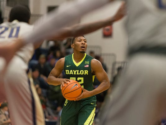 Baylor guard King McClure (22) looks to pass the ball over Randall forward Dante Lewis (20) in the first half of an NCAA college basketball game in Fort Hood, Texas, Saturday, Dec. 9, 2017. (AP Photo/Stephen Spillman)