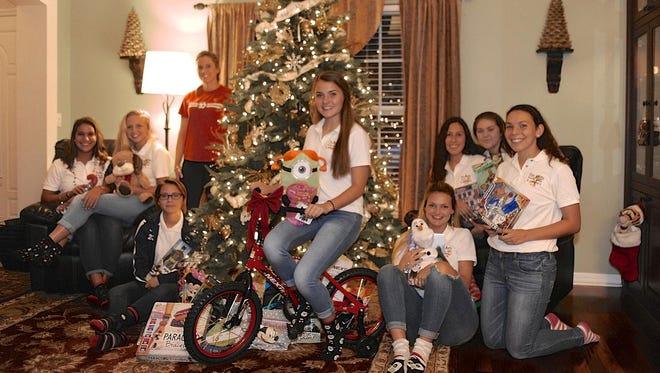 "The Eau Gallie High School girls soccer team works together on their annual ""Christmas for a Family."""