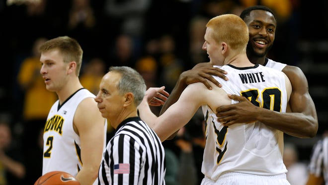 Iowa center Gabriel Olaseni and Iowa forward Aaron White hug as they get ready to exit the game during the second half of an NCAA college basketball game against Northwestern, Saturday, March 7, 2015, in Iowa City, Iowa. Iowa won 69-52.