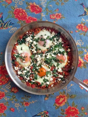 Eggs simmered in tomato sauce, with spinach and feta, make a hearty breakfast dish.
