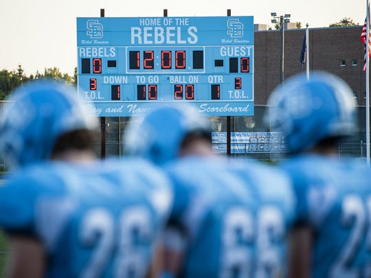 The South Burlington Rebels football team gathers on the sidelines at the start of a game against CVU in South Burlington on Friday.