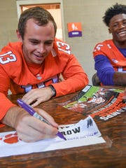 Clemson wide receiver Hunter Renfrow, left, keeps a tally of how many Sports Illustrated magazine covers he signs near wide receiver Tee Higgins, right, during fan day at Memorial Stadium in Clemson on Sunday.