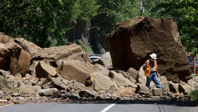 "A worker makes his way through rocks on the Historic Columbia River Highway on Thursday, June 5, 2014, east of Portland, Ore. State transportation spokesman Don Hamilton said about 1,000 cubic yards of rock and dirt fell Thursday morning, including what he described to The Oregonian as ""one very large rock."" He says the highway will remain closed Thursday and Friday and probably into the weekend. (AP Photo/The Oregonian, Beth Nakamura)"