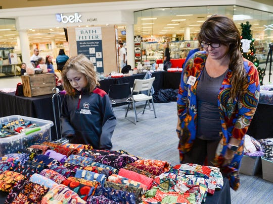Trace Gibson, left, and his mother Beth Gibson look at her Kiss My Glass business booth display at the Anderson Mall during Black Friday in Anderson.