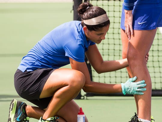 A trainer works on Florida Gulf Coast University's Sara Kelly as she starts to cramp during the Atlantic Sun Conference Finals at FGCU in Fort Myers, Fla., on Sunday, April 23, 2017.