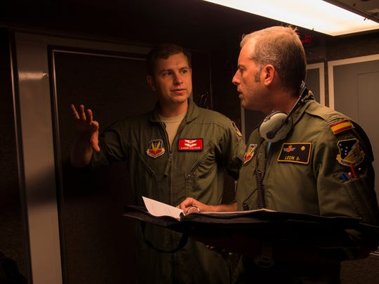Maj. Aaron, a 29th Attack Squadron MQ-9 Reaper instructor pilot, left, and Maj. Jaime, a Spanish air force student pilot, right, discuss MQ-9 flight procedures at Holloman Air Force Base, NM on April 19, 2017. Spain is currently participating in essential training here at the MQ-9 formal training unit.
