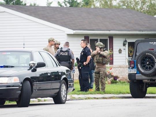 Law enforcement officers gear up near the scene of