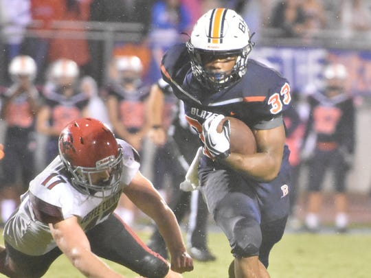 Blackman's Master Teague barrels past Coffee County defenders during Friday's Blaze win.